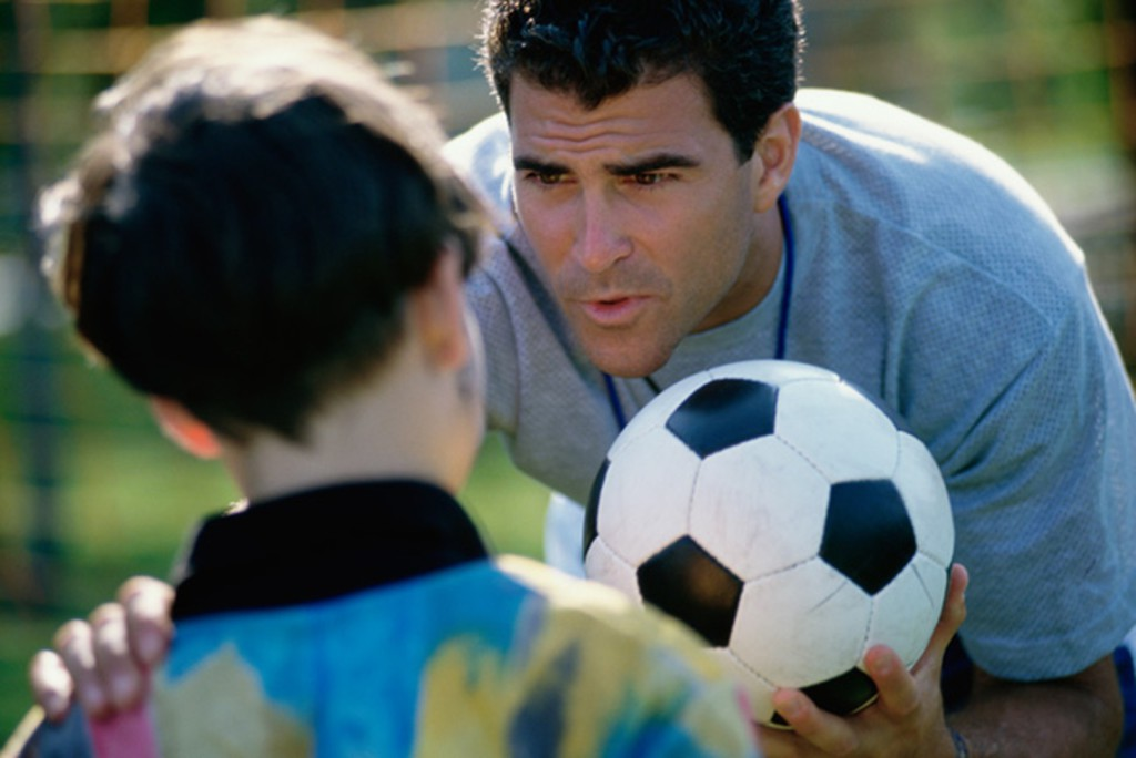 Soccer coach standing with his hand on a boy's sho